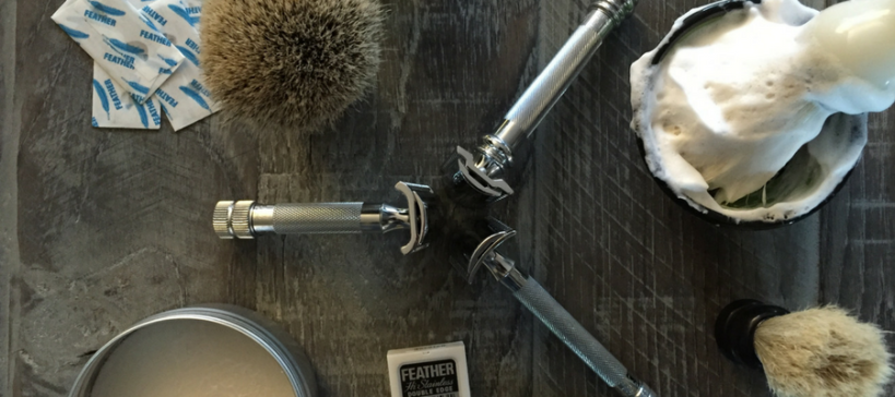 Blog header photograph of traditional wet saving gear including three double edge safety razors, a shave brush and safety razor blades with a rustic barn wood background. by Shave Valet Saskatoon YXE