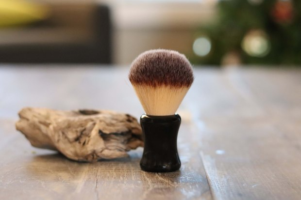 A synthetic bristle shaving brush with a black injection moulded handle.